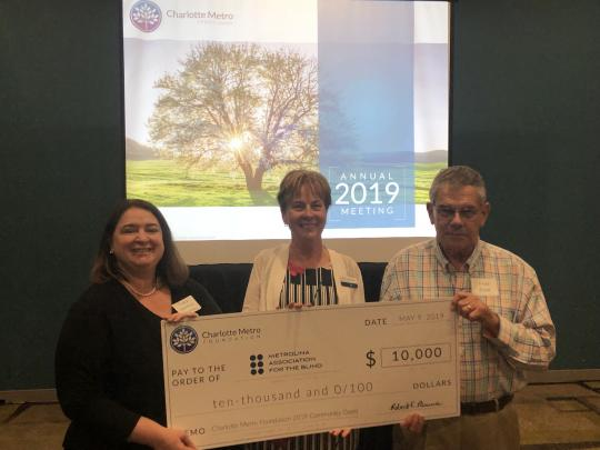 Image of Tracy Libertino (CEO), Laura Park-Leach (Sr VP, VRS) and Fred Funk (Board Chair) at the Charlotte Metro Annual meeting holding up a large check for the grant award.