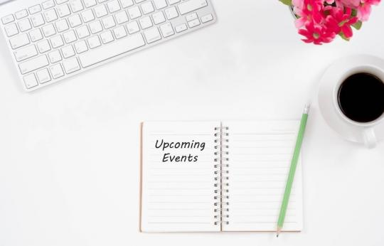 "Caption:  White desk with white keyboard, cup of coffee, pink flowers, green pencil and a notebook that reads, ""upcoming events."""