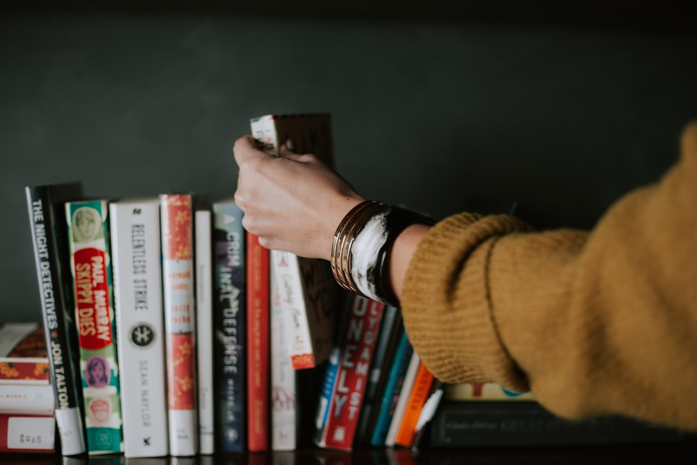Image of woman reaching for a book on a bookshelf